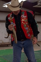 A member of the Shortgrass Rattlesnake Association holds a rattlesnake up before members of the 97th Air Mobility Wing, April 15, 2019, at Altus, Okla. Each Committee of 100 dinner is different and meant to showcase an aspect of the local culture in Altus.