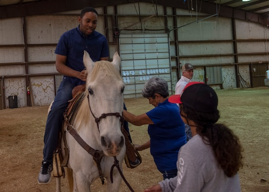 A student from the 97th Training Squadron rides a horse during the quarterly Committee of 100 dinner, April 15, 2019, at Altus, Okla. After the dinner and introductions, the members from the 97th Air Mobility Wing were able to ride horses and a mechanical bull while children jumped in bounce houses.