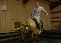 A student from the 97th Training Squadron rides a mechanical bull during the quarterly Committee of 100 dinner, April 15, 2019, at Altus, Okla. More than 300 base members attended the event, showcasing a strong bond between the local community and the 97th Air Mobility Wing.