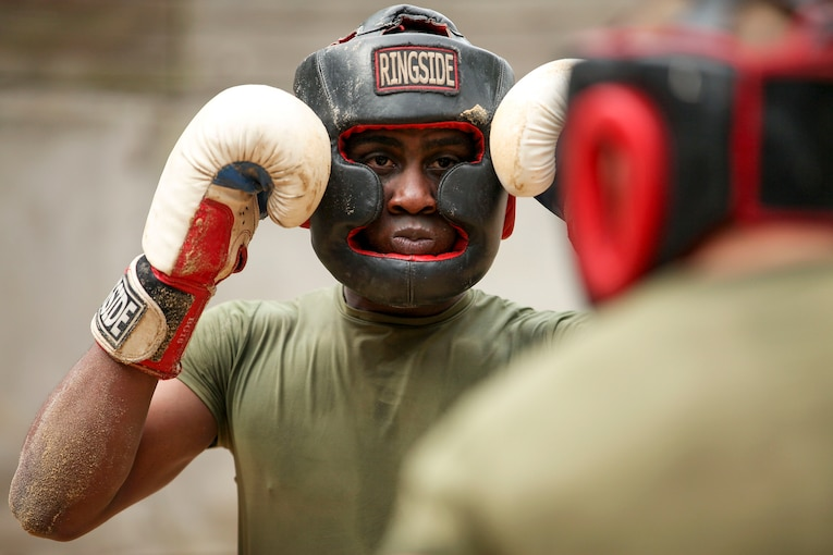 A Marine Corps recruit wearing protective headgear and boxing gloves holds up his fists while facing an opponent.