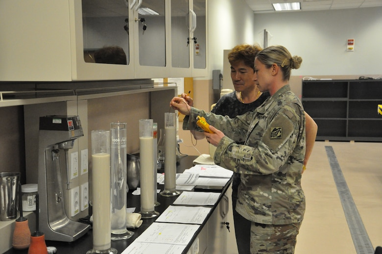 Staff Sgt. Kyla Stewart, a technical engineer in the Far East District (FED) materials testing laboratory learns the correct testing techniques from FED's material engineer, Song, Un-ho, April 11 at the Far East District headquarters, Camp Humphreys, Korea.