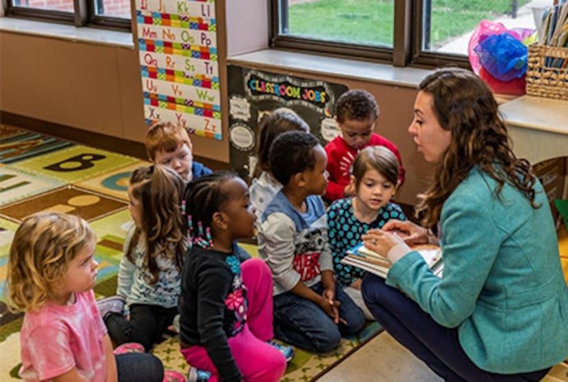 Children gather around on classroom rug surrounding guest speaker