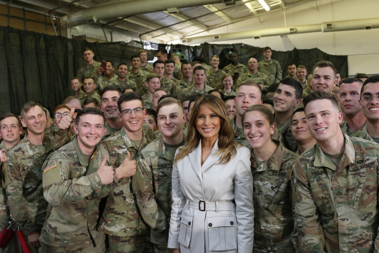 First Lady Melania Trump poses for a picture with a group of soldiers.