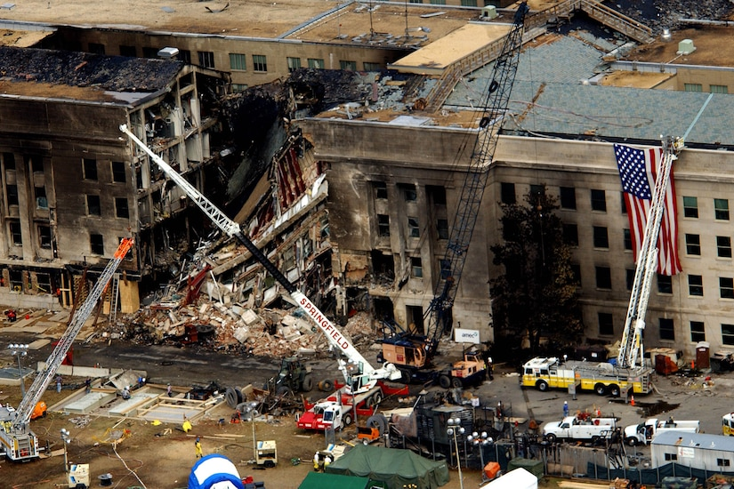 An aerial view of the charred and partially collapsed Pentagon, with fire trucks and emergency crews working around rubble.