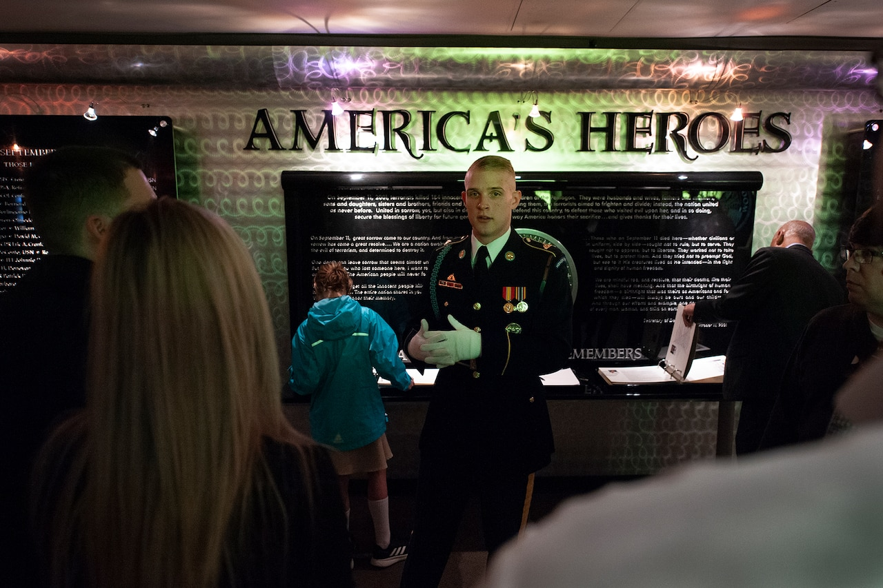 "A soldier stands in front of a display that reads ""America's Heroes."""