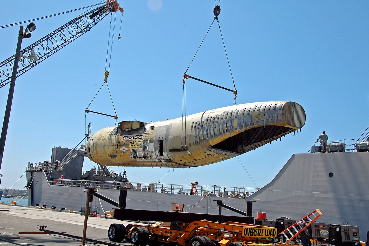 A crane lifts a fuselage to a ship.