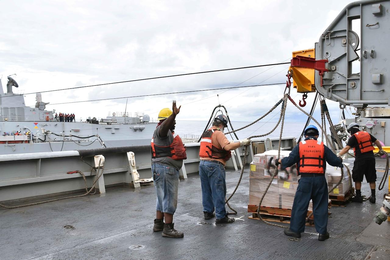 Men prepare pallet loads to be hoisted