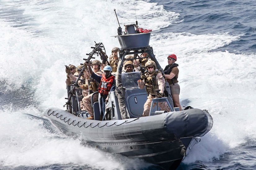 Troops stand in a speeding boat.