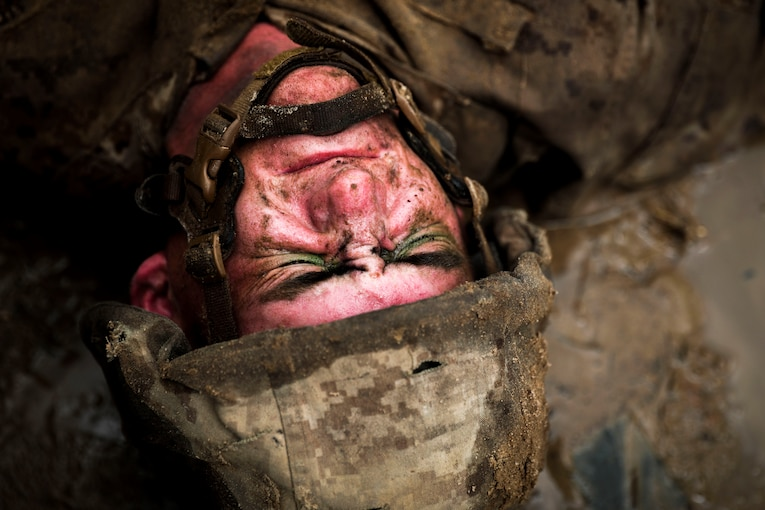 A Marine grimaces as he lays face-up in the sand.