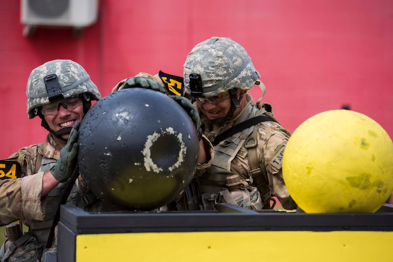 Two airmen position a large ball onto a platform.