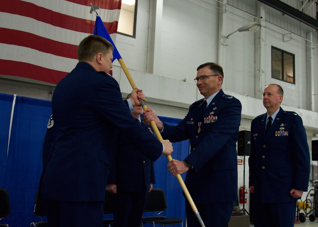 Col. John O'Connor (middle) relinquishes command of the 174th Mission Support Group (MSG) to Lt. Col. Michael Adamitis (right), former Deputy Maintenance Commander, during a change of command ceremony at Hancock Field Air National Guard Base April 7. (U.S. Air National Guard photo by Staff Sgt. Duane Morgan)