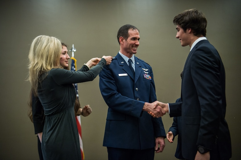 Lt. Col. Christopher Spinelli is joined by his family to assist with pinning on his new rank of Colonel, Mar. 2, 2019, Scott Air Force Base, Illinois during his promotion ceremony. (U.S. Air Force photo by Master Sgt. Christopher Parr)