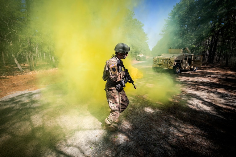 A soldier walks through yellow smoke.