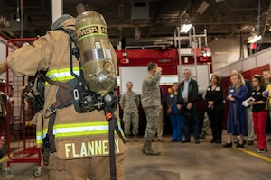 U.S. Air Force firefighter gives crowd demonstration of gear.