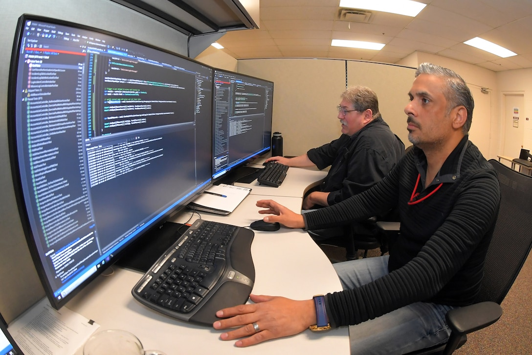 (Left to right) Mark Morris and Raheem Alhamdani, software engineers, 517th Software Engineering Squadron, perform paired programming March 25, 2019, at Hill Air Force Base, Utah. This new paired programming approach is part of a new workflow system and software development methodology to significantly reduce the time it takes to deliver software to customers. (U.S. Air Force photo by Todd Cromar)