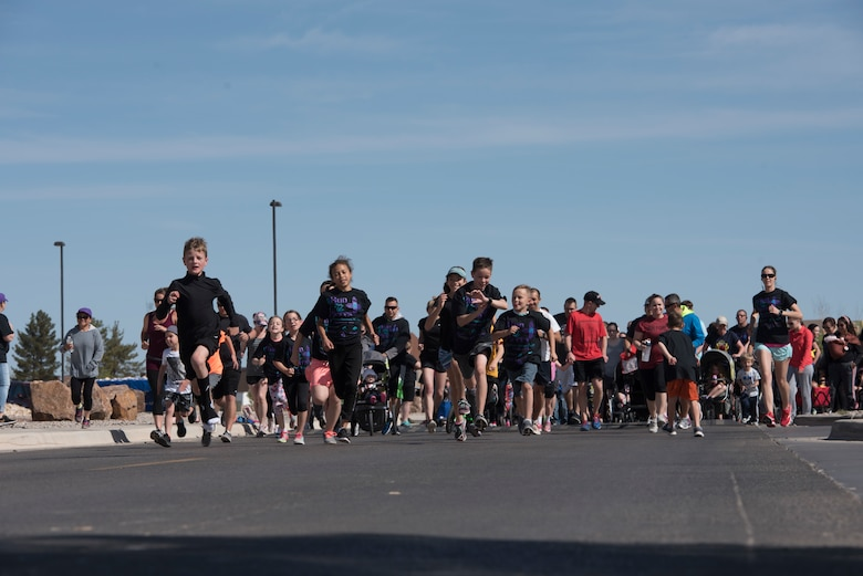 Participates take off from the starting line of an Autism Awareness fun run on Holloman Air Force Base, April 6, 2019. Over 750 people participated in the fun run and children's carnival. (U.S. Air Force Photo by Staff Sgt. Timothy Young)