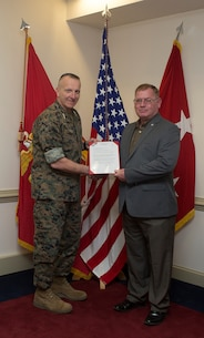 Harold W. Melching, branch head, Materiel Management Branch, Marine Corps Logistics Command, receives 2018 Marine Corps Civilian Logistician of the Year Award citation from Lieutenant General Charles G. Chiarotti, deputy commandant for Installation and Logistics, during a ceremony held at the Pentagon, March 28.