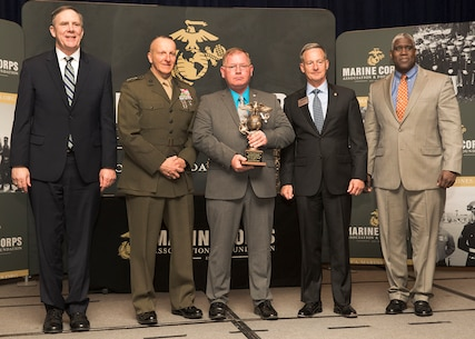 Harold W. Melching, center, branch head, Materiel Management Branch, Marine Corps Logistics Command, poses for a photo holding the 2018 Marine Corps Civilian Logistician of the Year Award he was awarded at the annual Marine Corps Association and Foundation Logistics Excellence Awards Dinner, March 28.
