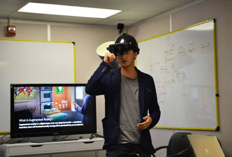 One of the innovating startup representatives wears a hard hat with see-through VR goggles that help to display a digital work center that can assist with working in a busy environment.