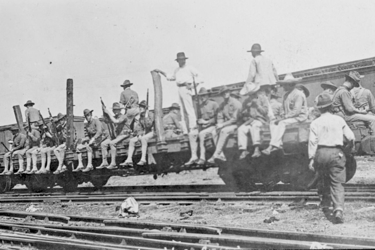 Veracruz Marines ride on a flat car.