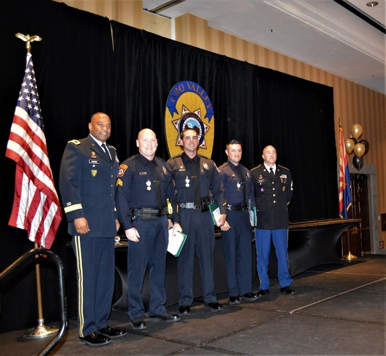 Brig. Gen. Kevin Vereen, deputy commanding general, United States Army Recruiting Command, poses with (from left to right) Sergeant Robert Goddard, Officer Jacob Taylor, Officer Donald Topar and Sgt. 1st Class Todd Miller, station commander, Foothills Recruiting Station, during an award ceremony, April 12, El Conquistador Hilton, Tucson, Ariz. The trio of Goddard, Taylor and Topar, all serving the Oro Valley Police Department, helped save Miller's life, when he suffered a heart attack in traffic, July 18, 2018. All three were awarded the Army Commander's Award for Public Service Medal by Vereen for their actions. (U.S. Army Photo by Mike Scheck, USAREC Public Affairs)