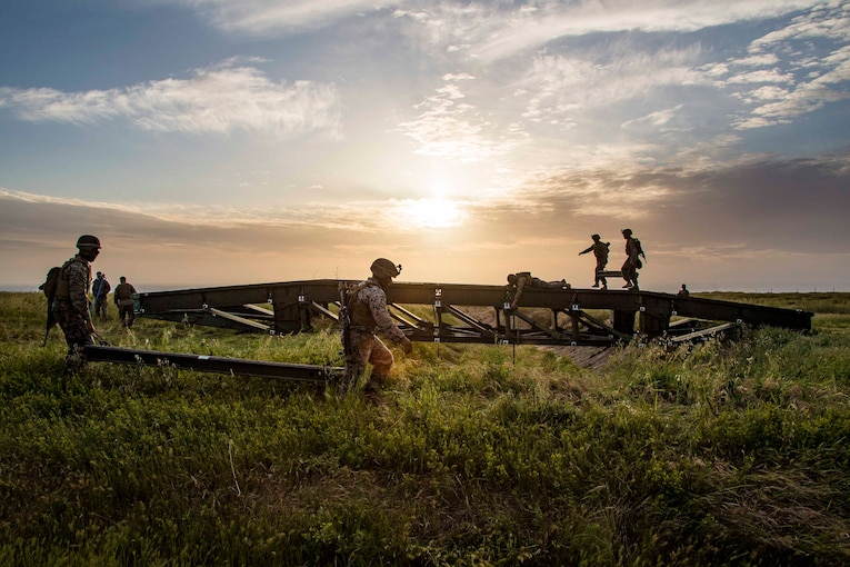 A group of Marines lift large metal pieces in a grassy field.