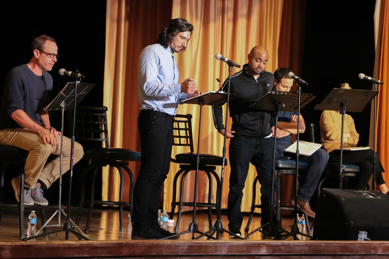 Actors sit and stand on a stage during a performance.