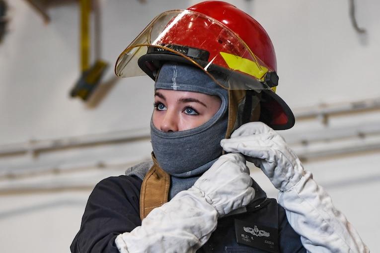 A sailor prepares for a drill on a ship.