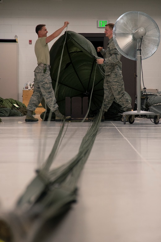 Senior Airman Will Lipscomb, left, and Airman 1st Class Tyler Pitts, both 39th Aerial Port Squadron air transportation technicians, practice inspecting a G-12 parachute at Peterson Air Force Base, Colorado, April 16, 2019. The