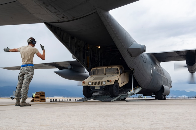Tech. Sgt. Russell Hudson, a 39th Aerial Port Squadron air transportation technician, directs a vehicle as it is backed into a C-130 Hercules aircraft during an engine-running onload at Peterson Air Force Base, Colorado, April 17, 2019.