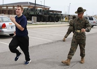 Sergeant Matthew Schihl, a drill instructor with Marine Corps Recruit Depot San Diego, California, motivates a poolee to run faster during the combat fitness test at an all-hands pool function. Recruiting Station Indianapolis hosted the pool function to simulate recruit training, while preparing  the poolees to deal with the stress and high tempo during the 13-week training regimen. (Official U.S. Marine Corps photo by Sgt. Carl King/Released)