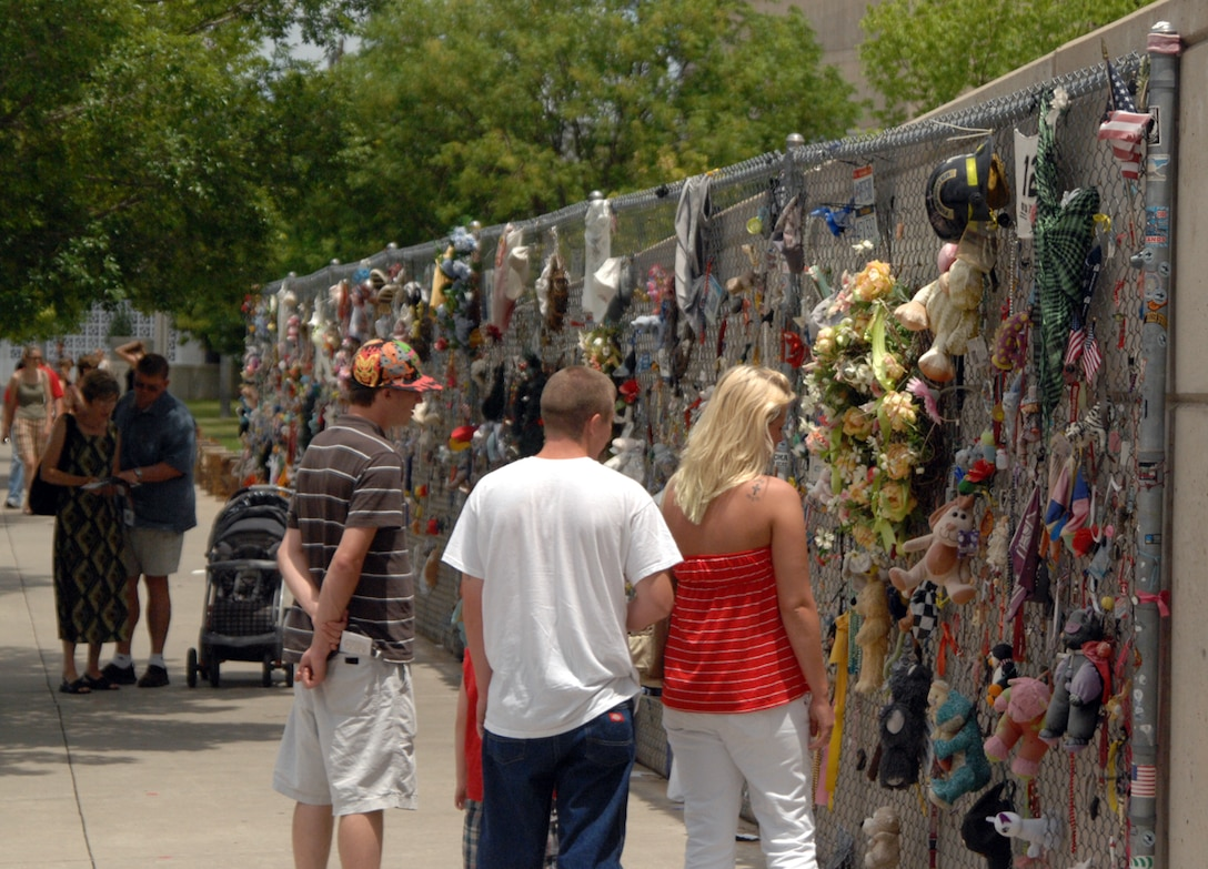 Visitors pay homage to the 168 victims of the April 19, 1995 bombing of the Alfred P. Murrah Federal Building in Oklahoma City, Okla. The memorial fence stretches more than 200 feet and is tribute which gives people the opportunity to leave tokens of remembrance. (U.S. Air Force photo)