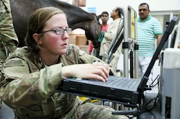 Sgt. Kelsey Wheatley, a radiology specialist from the 64th Brigade Support Battalion, 3rd Armored Brigade Combat Team, 4th Infantry Division, looks at the x-ray image she just scanned of a horse's leg at the Kuwait Ministry of Defense's Equestrian Center in Kuwait City on April 9, 2019. The 64th BSB and the KMOD have an ongoing partnership in which 64th BSB is able to provide portable x-ray equipment that enables the KMOD to thoroughly assess its horses.