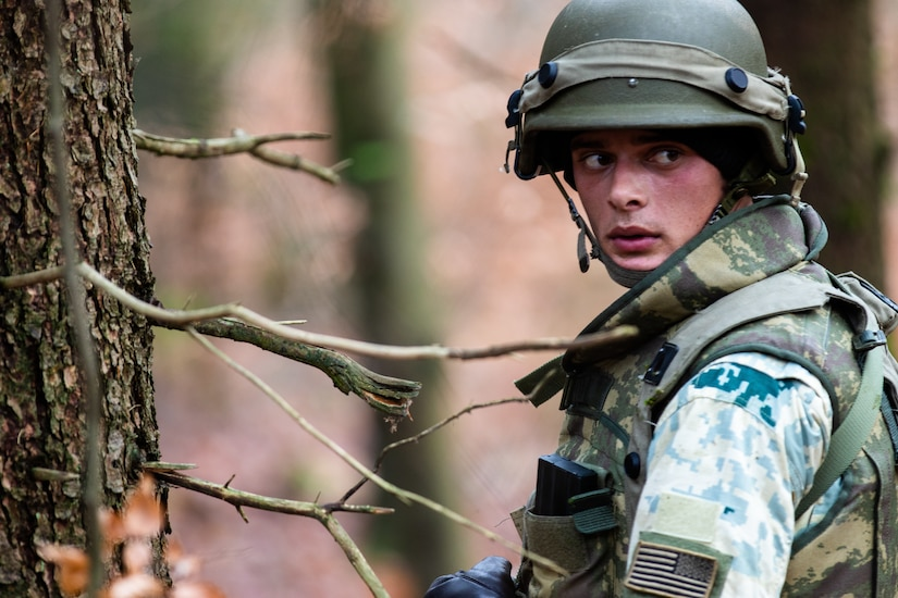 A soldier in the woods looks rearward.