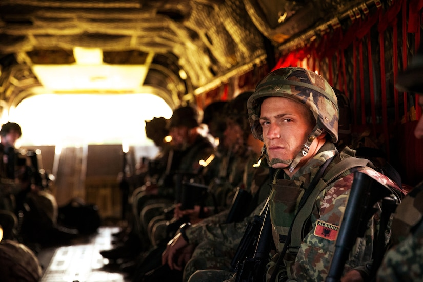 An Albanian service member sits with others in the rear of an aircraft.