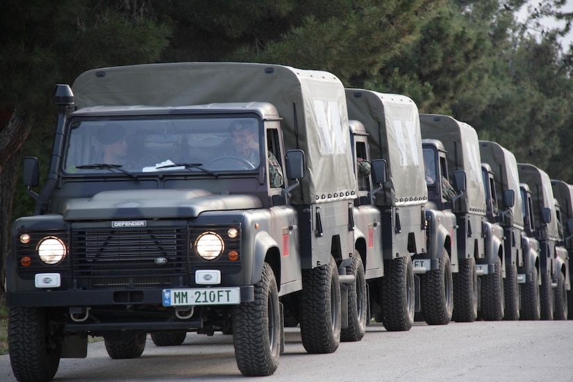 Albanian military vehicles travel in a convoy.
