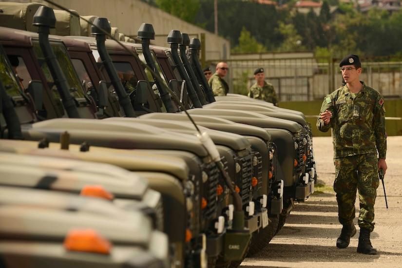 An Albanian service member walks alongside military vehicles.