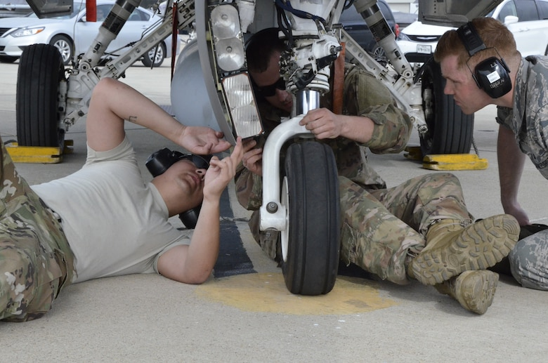 Senior Airman Collin Ries, Tech. Sgt. Davis Oetken, and Senior Airmen Andrew Staufer, Structural Repair Specialists with the 114th Maintenance Squadron evaluate the nose gear of an F-16C Fighting Falcon during Lobo Plummet at Marine Corps Air Station Miramar, California, March 2019.