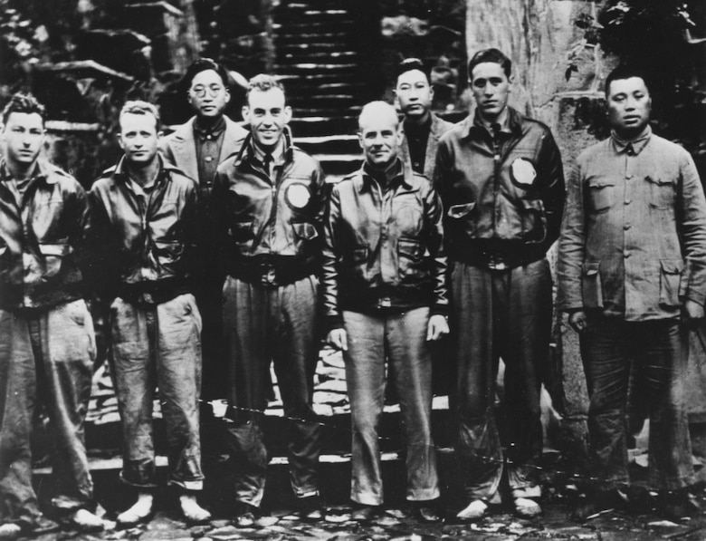 Doolittle (center) with members of his crew and Chinese officials following their bailout near Quzhou, China.  On 18 April 1942, airmen of the US Army Air Forces, led by Lt. Col. James H. (Jimmy) Doolittle, carried the Battle of the Pacific to the heart of the Japanese empire with a surprising and daring raid on military targets at Tokyo, Yokohama, Yokosuka, Nagoya, and Kobe. This heroic attack against these major cities was the result of coordination between the Army Air Forces and the US Navy, which carried the sixteen North American B-25 medium bombers aboard the carrier USS Hornet to within take-off distance of the Japanese Islands. Here, a pair of alert escorts follow the USS Hornet to protect her lethal cargo of B-25 bombers. (Courtesy Photo)