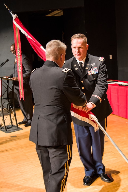 Lt. Gen. Todd Semonite (at left), chief of engineers and commanding general of the U.S. Army Corps of Engineers, passes the Huntsville Center colors to Lt. Col. H. W. Hugh Darville, Huntsville Center's incoming commander, during a change-of-command ceremony April 18, 2019, at the University of Alabama in Huntsville's Chan Auditorium in Huntsville, Alabama.
