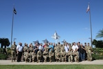 More than 40 Pacific based munitions experts pose in front of the Bishop Point Memorial for a group photo located behind the Historic Hickam Officers Club for the first ever Pacific Theater Munitions Summit, hosted by the 8th Theater Sustainment Command. Apr. 4, 2019. The summit served as a forum for the munitions community to come together to collaborate and define problems and shortcomings of facilities in the Pacific theater.