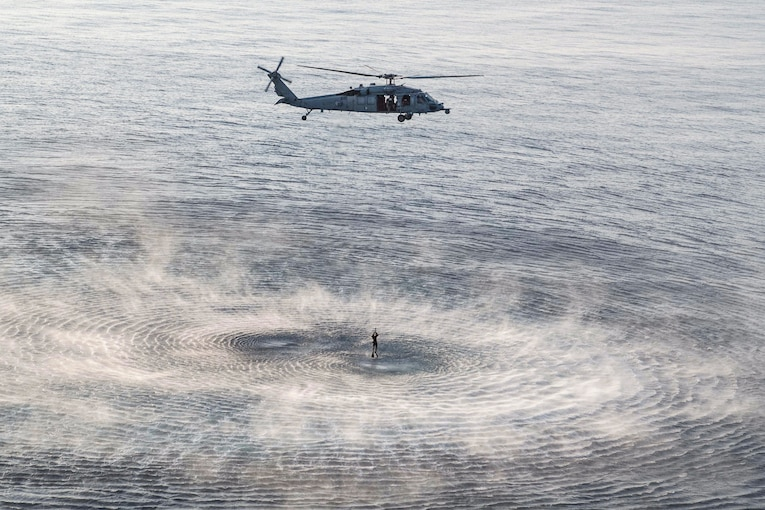 A helicopter lifts a sailor out of the water, creating a circular wake around him.