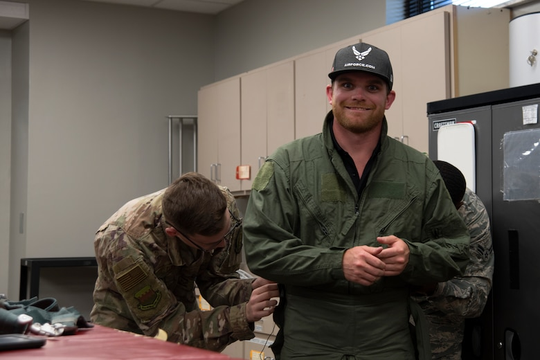 U.S. Air Force Senior Airman Matthew Day, left, and Airman 1st Class Orlando Harris, right, 20th Operations Support Squadron aircrew flight equipment technicians, adjust the fit of a G-suit worn by Conor Daly, Air Force Honda race car driver, at Shaw Air Force Base, S.C., April 15, 2019.