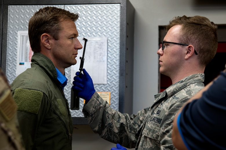 U.S. Air Force Airman 1st Class Carson Buice, 20th Operations Support Squadron aircrew flight equipment technician, takes measurements of Townsend Bell, sports commentator and professional race car driver, at Shaw Air Force Base, S.C., April 15, 2019.