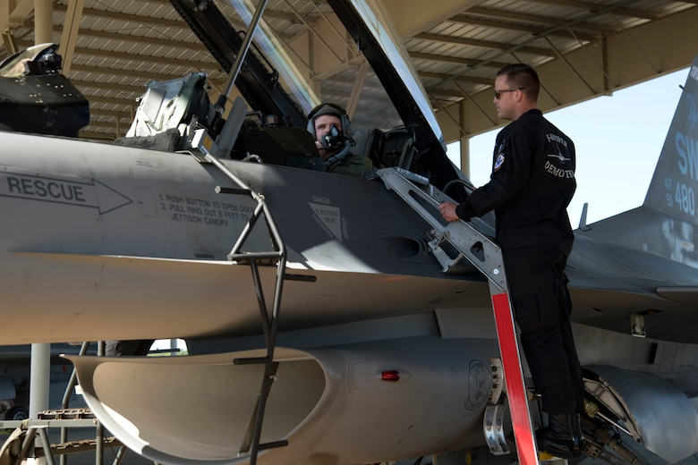 U.S. Air Force Staff Sgt. Trevor Griswold, F-16 Viper Demonstration Team electrical and environmental systems craftsman, stands by as Conor Daly, Air Force Honda race car driver, secures his helmet at Shaw Air Force Base, S.C., April 16, 2019.