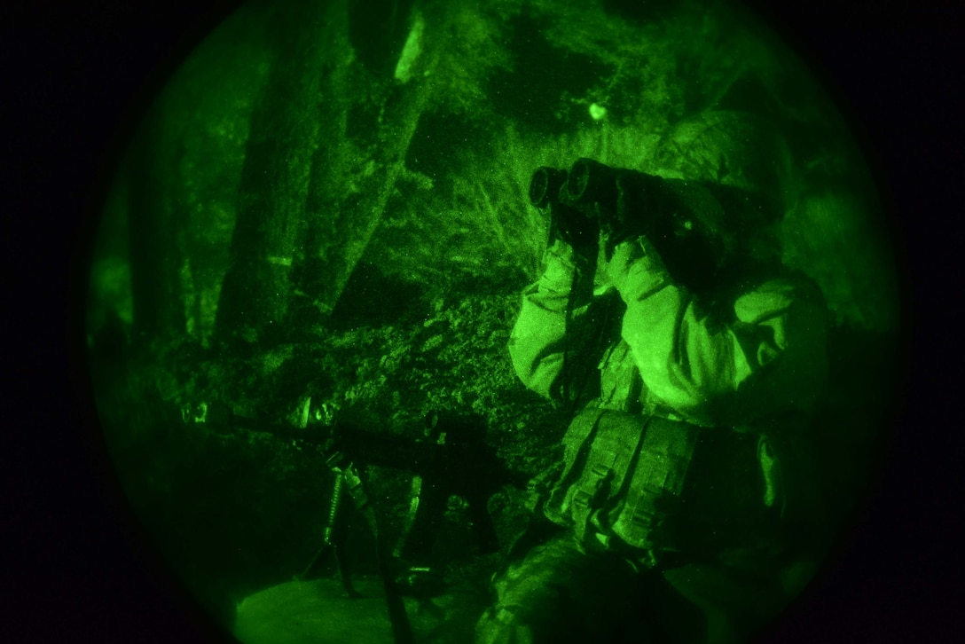 An Airmen looks through binoculars at night