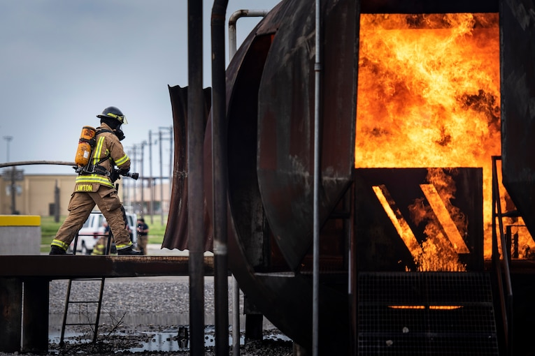 A firefighter holding a hose stands outside a burning fuselage during training.