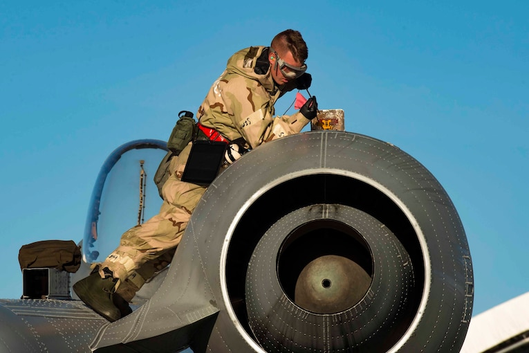 An airman lies on top of an aircraft holding an oil stick towards an opening.