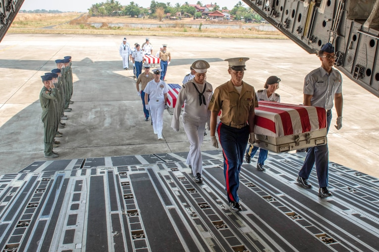 Service members carry coffins into an aircraft.