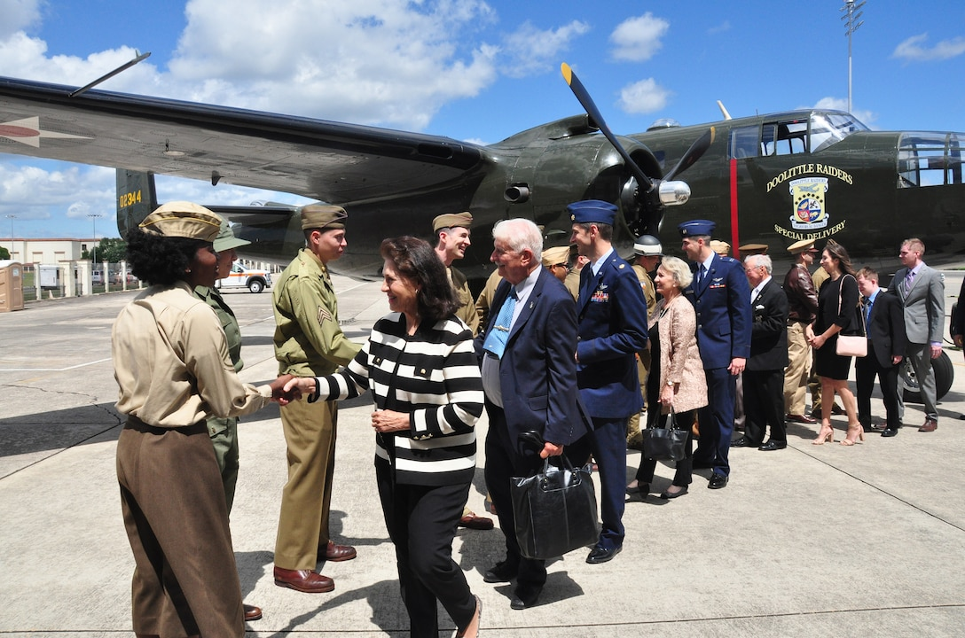 """The family of retired U.S. Air Force Lt. Col. Richard """"Dick"""" E. Cole shake hands with Airmen dressed in WWII uniforms at a B-25 Mitchell static display during a memorial service for their father at Joint Base San Antonio-Randolph, Texas, April 18, 2019."""